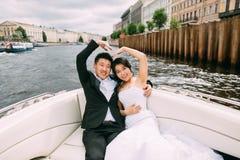 Les jeunes mariés flottent sur un bateau Photo stock