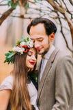 Les jeunes mariés heureux étreignant doucement dans les bois d'automne se ferment  Images libres de droits