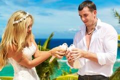 Les jeunes mariés heureux avec les colombes blanches sur une plage tropicale u Photos libres de droits