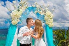 Les jeunes mariés heureux avec les colombes blanches sur une plage tropicale u Image libre de droits
