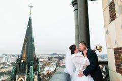 Les jeunes mariés heureux de nouveaux mariés ont un moment sensuel sur le balcon de la vieille cathédrale gothique Photo libre de droits