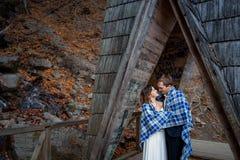 Les jeunes mariés heureux enveloppés dans la couverture étreignent doucement sur le pont en bois aux montagnes Fond de forêt d'au Images stock