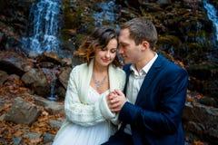 Les jeunes mariés heureux tenant doucement des mains se ferment  Cascade sur le fond image libre de droits