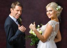 Les jeunes mariés montrent un geste de la bonne chance Photo libre de droits