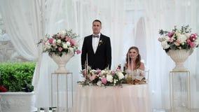 Les jeunes mariés ont l'amusement au banquet l'épousant Jeunes couples les épousant affectueux dans la tente clips vidéos