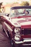 Les jeunes mariés ont l'amusement derrière la roue de la rétro voiture rouge de vintage mariage Images stock
