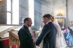 Les jeunes mariés parlent au prêtre Photos stock