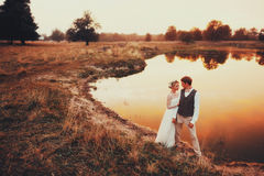 Les jeunes mariés posant dans la perspective du lac dans le coucher du soleil rouge plan global Image stock