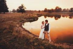 Les jeunes mariés posant dans la perspective du lac dans le coucher du soleil rouge plan global Photographie stock