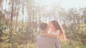 Les jeunes mariés posent dans la forêt que le jeune marié joyeux soulève la jeune mariée et l'entoure dans les rayons de banque de vidéos