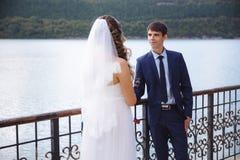 Les jeunes mariés s'admettent dans l'amour dans la perspective de la rivière Un couple tient les mains, une fille dans a Images stock