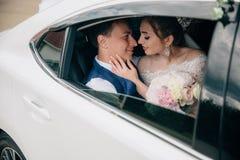 Les jeunes mariés s'asseyent dans le siège arrière de la voiture, la fille tiennent un bouquet des fleurs dans des ses mains image libre de droits