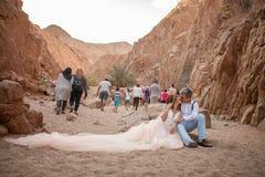 Les jeunes mariés s'asseyent et embrassent en canyon contre le contexte des touristes passant par Photo stock