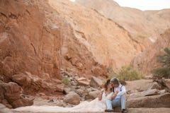 Les jeunes mariés s'asseyent et embrassent en canyon sur le fond des roches Photographie stock