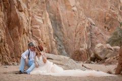 Les jeunes mariés s'asseyent et sourient en canyon sur le fond des roches Photos stock