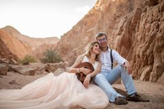Les jeunes mariés s'asseyent et sourient en canyon sur le sable sur le fond des roches Image libre de droits