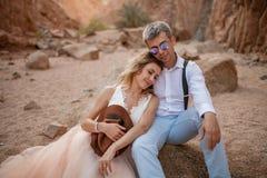 Les jeunes mariés s'asseyent et sourient en canyon sur le sable sur le fond des roches closeup Photographie stock libre de droits