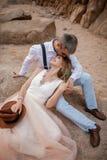 Les jeunes mariés s'asseyent et sourient sur le sable en canyon sur le fond des roches closeup Photo stock