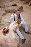 Les jeunes mariés s'asseyent et sourient sur le sable en canyon sur le fond des roches closeup Photos stock