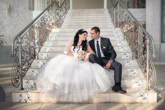 Les jeunes mariés s'asseyent sur l'escalier avant Photos libres de droits
