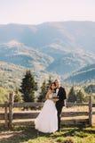 Les jeunes mariés se tenant sur le pont en bois en nature, embrassant près de la barrière avec le fond de montagne Photo stock