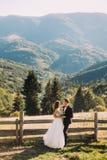 Les jeunes mariés se tenant sur le pont en bois en nature, embrassant près de la barrière avec le fond de montagne Photo libre de droits