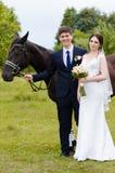 Les jeunes mariés se tiennent en parc près du cheval, épousant la promenade Robe blanche, ajouter heureux à un animal Fond vert Images libres de droits
