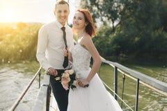 Les jeunes mariés se tiennent sur le pont Photos stock