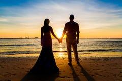 Les jeunes mariés sont les mains gardées sur une plage tropicale Silhoue Photo libre de droits