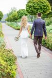Les jeunes mariés sont marchants et tenants des mains photos libres de droits