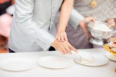 Les jeunes mariés sont scoop le riz du plat blanc, cuvette d'or élégante pour des jeunes mariés donnent la nourriture d'objectifs images stock