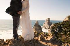 Les jeunes mariés sur la belle falaise près de l'océan Photographie stock