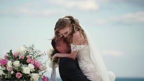 Les jeunes mari?s ? la c?r?monie l'?pousant Un jeune couple dans des supports d'amour ? la vo?te Wedding par la mer banque de vidéos