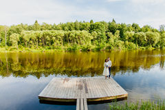 Les jeunes mariés se tiennent sur un pilier en bois près de l'étang Photographie stock libre de droits