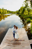 Les jeunes mariés se tiennent sur un pilier en bois près de l'étang Photos libres de droits