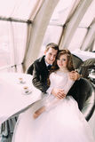 Les jeunes mignons ont marié des couples étreignant se reposer dans le café et regarder l'appareil-photo Photo stock