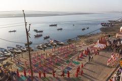 Les jeunes moines indous conduisent une cérémonie pour rencontrer l'aube sur les banques du Gange, et soulèvent le drapeau indien photo stock