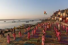 Les jeunes moines indous conduisent une cérémonie pour rencontrer l'aube sur les banques du Gange, et soulèvent le drapeau indien photos libres de droits