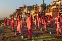 Les jeunes moines indous conduisent une cérémonie pour rencontrer l'aube sur les banques du Gange, et soulèvent le drapeau indien images libres de droits