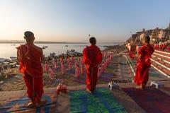 Les jeunes moines indous conduisent une cérémonie pour rencontrer l'aube sur les banques du Gange, et soulèvent le drapeau indien images stock