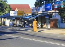 Les jeunes moines sont aumône de marche de matin dans Dalat photos stock