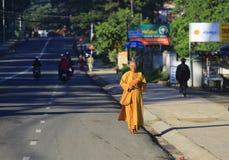 Les jeunes moines sont aumône de marche de matin dans Dalat photo stock