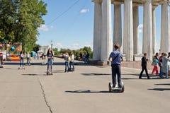 Les jeunes montant un Segway et un gyrometer sur l'asphalte sur Image stock