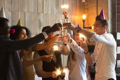 Les jeunes multi-ethniques célébrant les verres tintants de nouvelle année Image stock