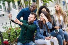 Les jeunes multi-ethniques prenant le selfie ensemble dans le backgr urbain Photographie stock libre de droits