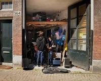 Les jeunes musiciens préparent dans le garage Image libre de droits