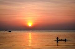 les jeunes nageant en atmosphère de coucher du soleil Photographie stock libre de droits