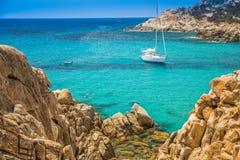 Les jeunes naviguant au schnorchel sur l'île de la Sardaigne avec les pierres rouges près de Chia échouent Photo stock