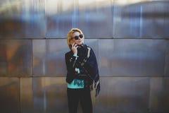 Les jeunes occasionnel-ont habillé la femme ayant la conversation de téléphone portable tout en attendant quelqu'un dehors Image stock