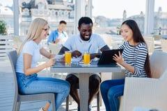 Les jeunes occupés positifs à l'aide de la tablette en café Photos stock